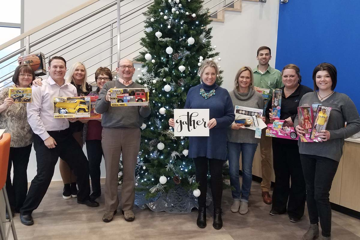 Accel Foundation - The Accel Team in Front of Holiday Tree While Holding Gifts for Charity